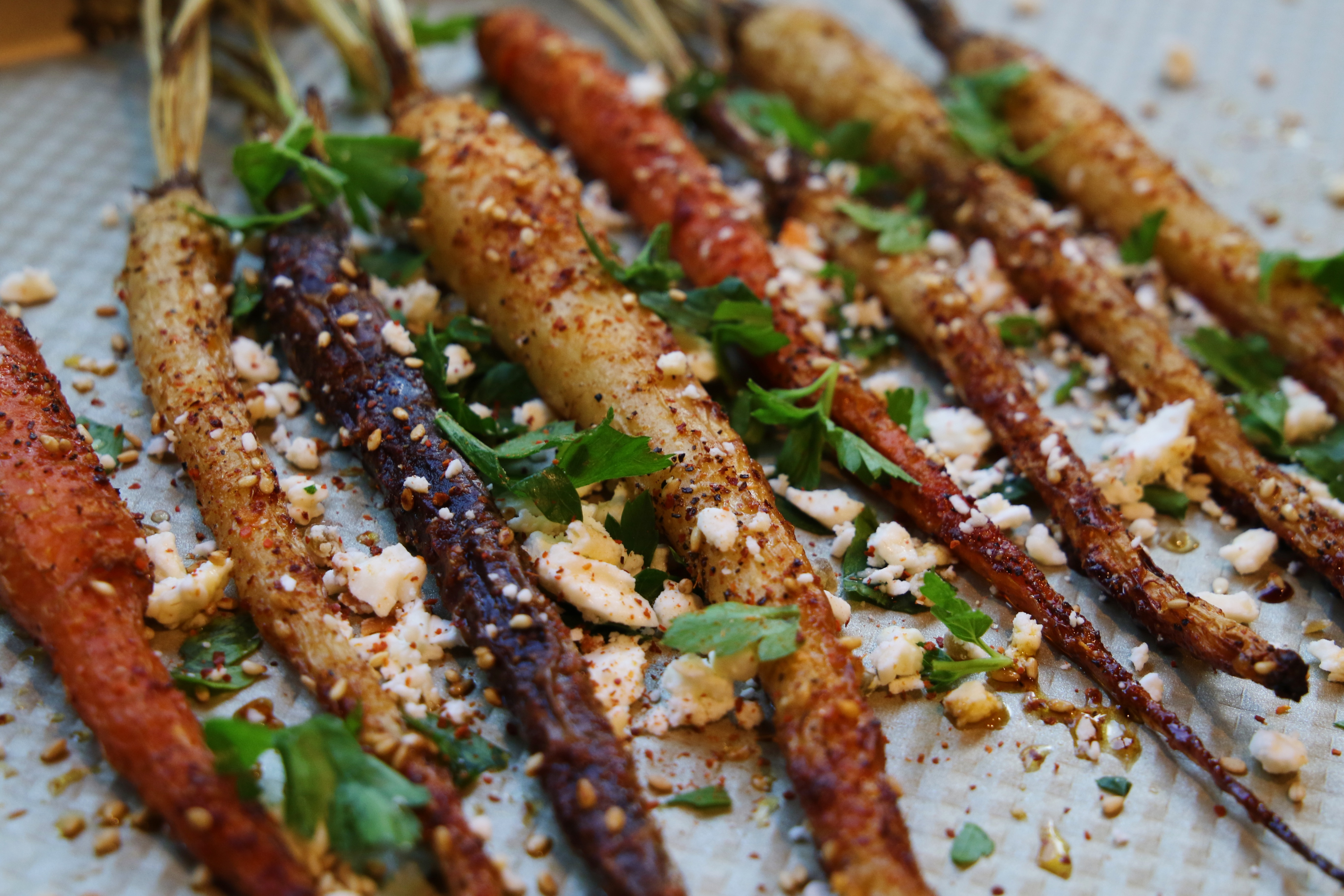 dinner side dish recipe of roasted rainbow carrots with spices and crumbled goat cheese
